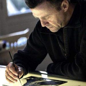 Een afbeelding van Ruud Harberts aan het brandschilderen in glasatelier ruud harberts.