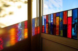 Een afbeelding van een glas-in-loodraam wat licht doorheen valt, gemaakt met de technieken brandschilderen en glas-in-lood | door glasatelier ruud harberts