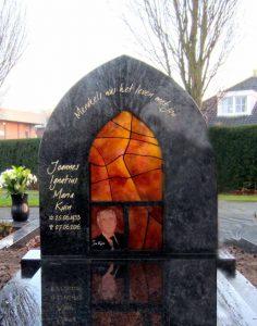 Een afbeelding van een grafmonument van natuursteen met een gebrandschilderd glas