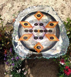 Een afbeelding van een gebrandschilderd symbool, dat boven een versteende boomstam zweeft